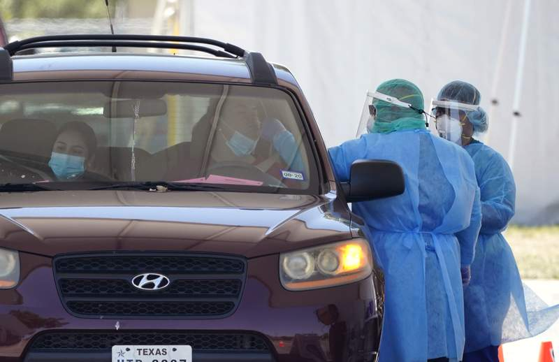 FILE - In this Aug. 14, 2020, file photo, medical personnel administer COVID-19 testing at a drive-thru site in San Antonio. The number of Americans newly diagnosed with the coronavirus is falling  a development experts credit at least partly to increased wearing of masks  even as the outbreak continues to claim nearly 1,000 lives in the U.S. each day. (AP Photo/Eric Gay, File)