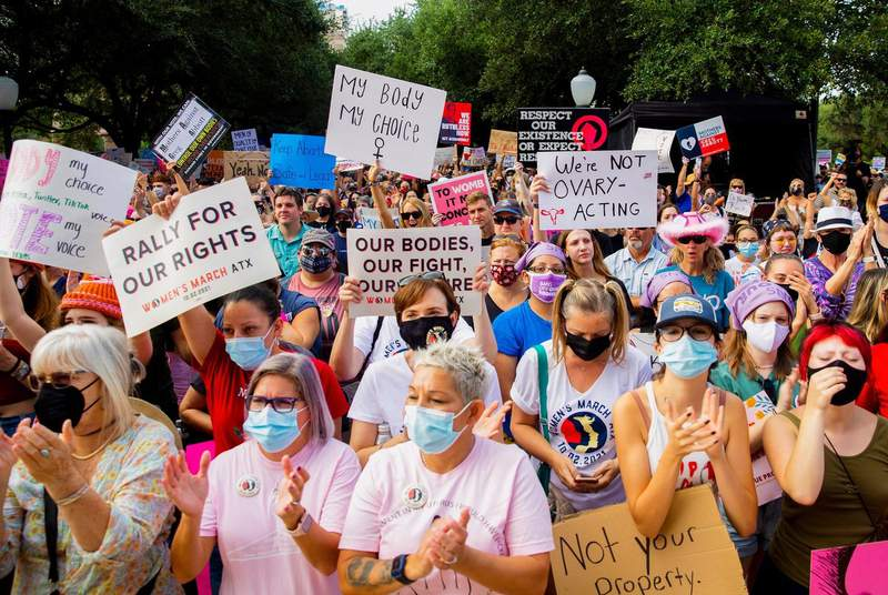 People hold signs and clap during the Womens March ATX at the Texas Capitol in Austin, Texas, on Saturday, Oct. 2, 2021. Thousands of people attended the rally in support of womens reproductive health and access to safe abortions.
