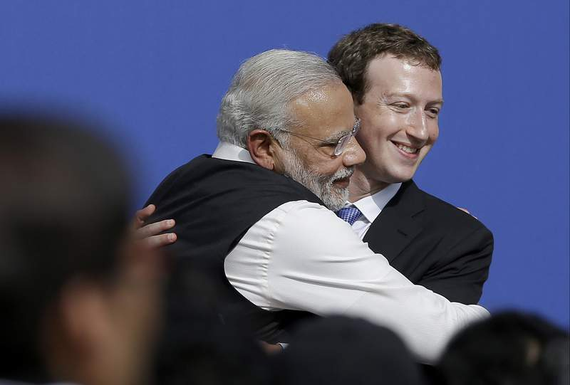 FILE - In this Sept. 27, 2015, file photo, Facebook CEO Mark Zuckerberg, right, hugs Prime Minister of India Narendra Modi at Facebook in Menlo Park, Calif. Facebook India executives were grilled Wednesday by members of a parliamentary committee on information technology over the company's alleged political bias and role in spreading hate speech in India. (AP Photo/Jeff Chiu, File)