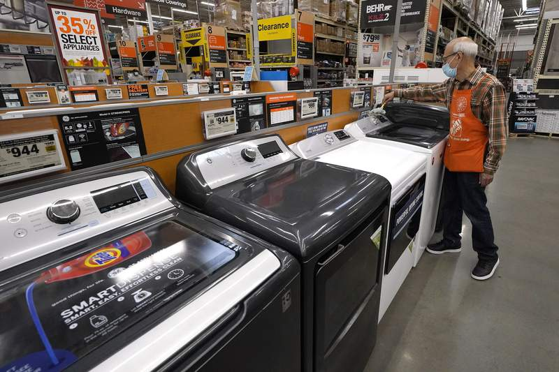 Worker Javad Memarzadeh, of Needham, Mass., right, dusts washers in a display, Thursday, Oct. 29, 2020, at a Home Depot location, in Boston.  Orders to U.S. factories for big-ticketed manufactured goods rose a moderate 0.9% in November with a key category that tracks business investment plans showing a gain. The Commerce Department said Wednesday, Dec. 23 that the November gain in orders for durable goods, items expected to last at least three years, followed stronger gains in recent months including a 3.8% rise in October.(AP Photo/Steven Senne)