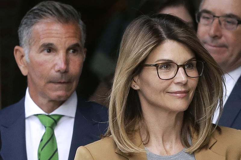 FILE - In this April 3, 2019 file photo, actress Lori Loughlin, front, and husband, clothing designer Mossimo Giannulli, left, depart federal court in Boston after facing charges in a nationwide college admissions bribery scandal. The famous couple pleaded guilty to charges in May 2020, and are scheduled to be sentenced on Friday, Aug. 21, 2020. (AP Photo/Steven Senne, File)