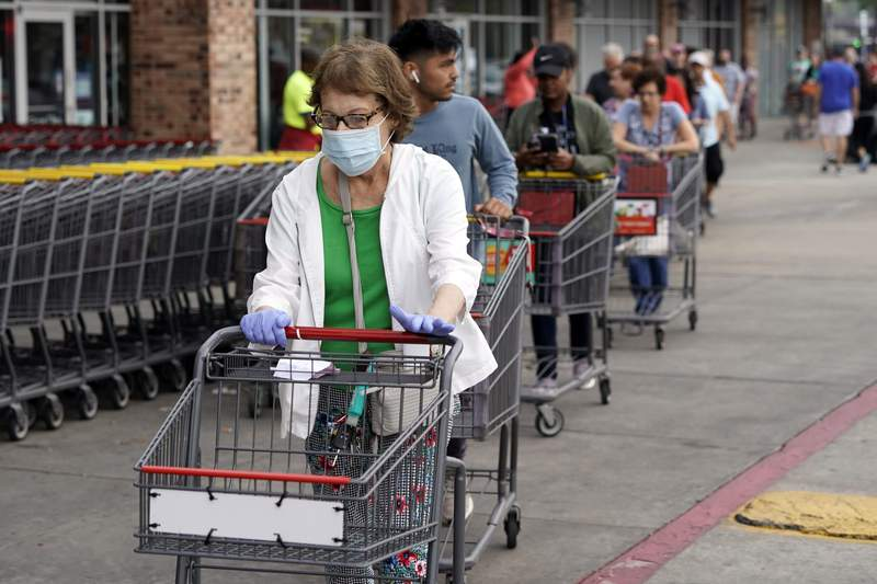 Ruth Flavelle wears a mask and gloves as she enters an H-E-B grocery after waiting in line with more than 150 people Tuesday, March 17, 2020, in Spring, Texas.  Grocery store executives and city officials reassured the community, on Monday, that plenty of food will be available in their stores and urged people not to stockpile groceries amid coronavirus concerns. (AP Photo/David J. Phillip)
