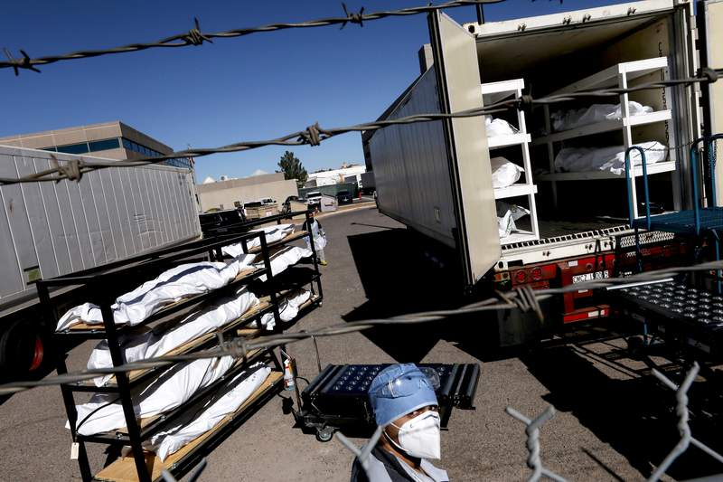 \A low-level inmate from El Paso County detention facility prepare to load bodies wrapped in plastic into a refrigerated temporary morgue trailer in a parking lot of the El Paso County Medical Examiner's office on November 16, 2020 in El Paso, Texas. The inmates, who are also known as trustees, are volunteering for the work and earn $2 per hour amid a surge of COVID-19 cases in El Paso. Texas surpassed 20,000 confirmed coronavirus deaths today, the second-highest in the U.S., with active cases in El Paso now well over 30,000. (Photo by Mario Tama/Getty Images)