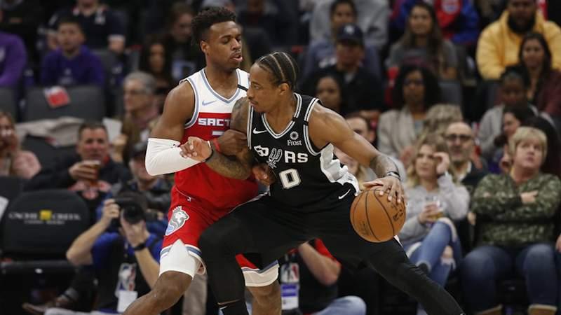 Sacramento Kings guard Buddy Hield, left, tries to stop the drive of San Antonio Spurs forward DeMar DeRozan during the first quarter of an NBA basketball game in Sacramento, Calif., Saturday, Feb. 8, 2020.