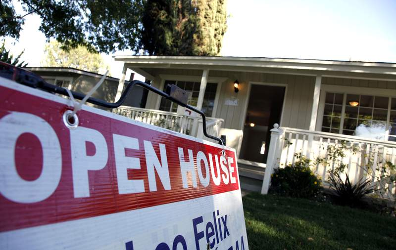 In this Nov. 4, 2010 photo, signs are posted for an open house on the front lawn of a home for sale in Los Angeles. Sales of previously owned homes slipped slightly in October as the housing market struggled in the face of high unemployment and tight credit. (AP Photo/Richard Vogel)