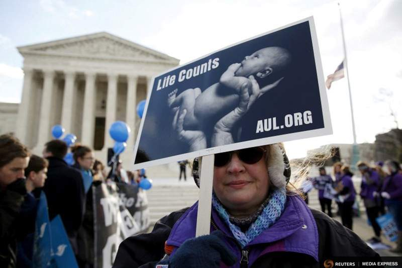 A protester holds up a sign in front of the U.S. Supreme Court on the morning the court takes up a major abortion case focusing on whether a Texas law that imposes strict regulations on abortion doctors and clinic buildings interferes with the constitutional right of a woman to end her pregnancy, in Washington March 2, 2016.