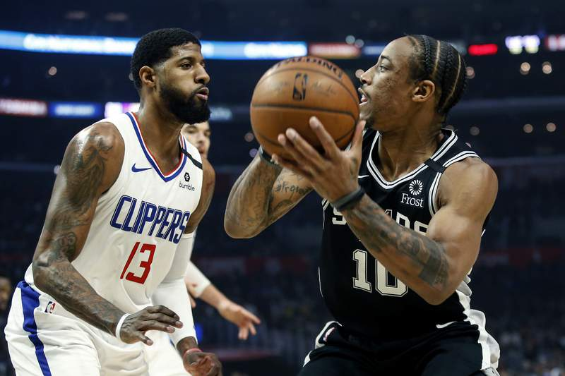 San Antonio Spurs' DeMar DeRozan (10) is defended by Los Angeles Clippers' Paul George (13) during the first half of an NBA basketball game, Monday, Feb. 3, 2020, in Los Angeles. (AP Photo/Ringo H.W. Chiu)