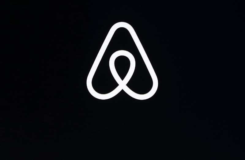 FILE - This Feb. 22, 2018, file photo shows an Airbnb logo during an event in San Francisco. Airbnb has raised the price of its shares ahead of its initial public offering this week, betting investors will pay more given its resiliency during the pandemic. In a government filing Monday, Dec. 7, 2020, Airbnb said it expects to price its shares between $56 and $60 each, up from a planned range of $44 to $50 issued last week. (AP Photo/Eric Risberg, File)