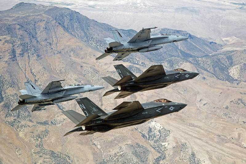 FILE - In this Sept. 3, 2015, file photo provided by the U.S. Navy, F-35C Lightning IIs, attached to the Grim Reapers of Strike Fighter Squadron (VFA) 101, and F/A-18E/F Super Hornets attached to the Naval Aviation Warfighter Development Center (NAWDC) fly over Naval Air Station Fallon's (NASF) Range Training Complex near Fallon, Nev. The U.S. Navy has concluded no significant environmental harm would result from its proposed tripling of the size of a Nevada bombing training range opposed by neighboring tribes, conservationists and at least one Democratic presidential candidate. (Lt. Cmdr. Darin Russell/U.S. Navy via AP, File)