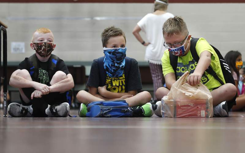 FILE - In this Aug. 5, 2020, file photo, wearing masks to prevent the spread of COVID19, elementary school students wait for classes to begin in Godley, Texas. As schools reopen around the country, their ability to quickly identify and contain coronavirus outbreaks before they get out of hand is about to be put to the test. (AP Photo/LM Otero, File)