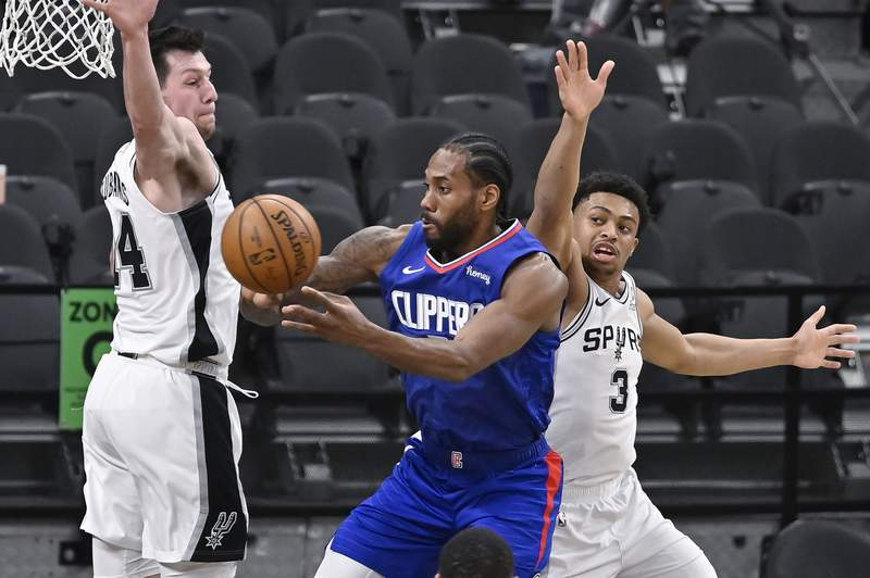 Los Angeles Clippers' Kawhi Leonard, center, passes the ball as he is defended by San Antonio Spurs' Drew Eubanks, left, and Keldon Johnson during the first half of an NBA basketball game on Wednesday, March 24, 2021, in San Antonio. (AP Photo/Darren Abate)