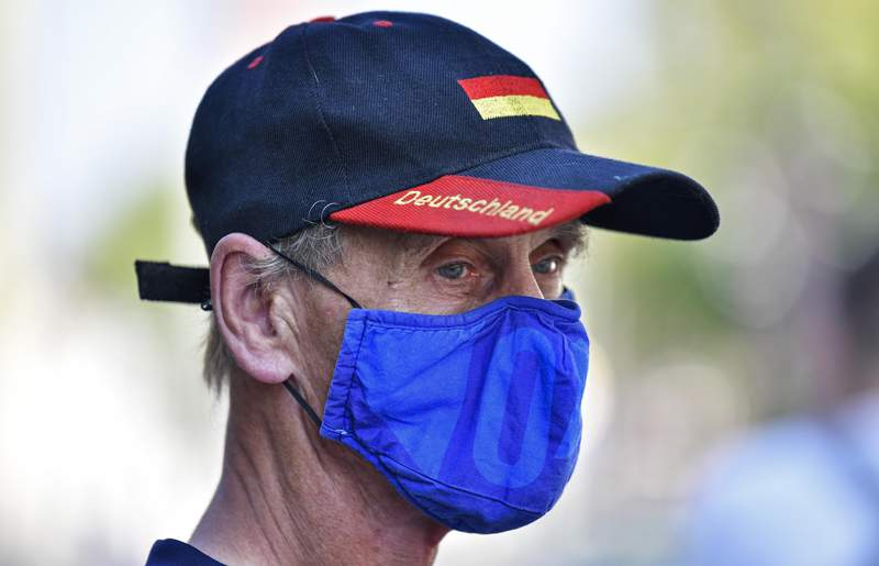"""Due to the new coronavirus pandemic a man wears a face mask of the German first division soccer team FC Schalke 04 and a hat with the word reading """"Deutschland"""" (Germany) in Gelsenkirchen, Germany, Wednesday, Aug. 12, 2020. (AP Photo/Martin Meissner)"""