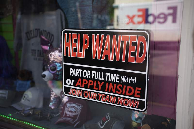 In this May 26, 2021 photo, a sign for workers hangs in the window of a shop along Main Street in Deadwood, S.D.  The U.S. working-age population shrank last year for the first time on record, as immigration slowed sharply, millions of Americans reached retirement age, and thousands died from the coronavirus.(AP Photo/David Zalubowski)