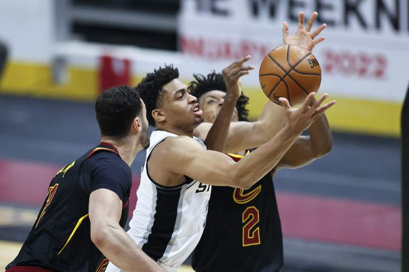 San Antonio Spurs' Keldon Johnson (3) grabs a rebound between Cleveland Cavaliers' Larry Nance Jr., (22) and Collin Sexton (2) in the first half of an NBA basketball game, Friday, March 19, 2021, in Cleveland. (AP Photo/Ron Schwane)