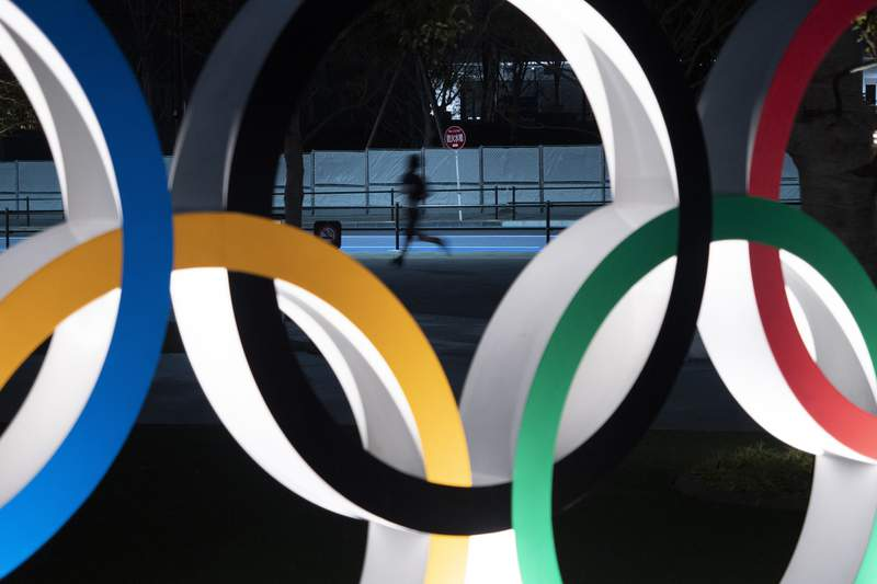 FILE - In this March 30, 2020, file photo, a man jogs past the Olympic rings in Tokyo. The chief executive of the Tokyo Olympics has promised transparency on Thursday, April 23, 2020, with the Japanese public over the cost of postponing the games until next year. Neither the Japanese Olympic organizers nor the International Olympic Committee has said what it will cost. Early estimates in Japan range between $2 billion and $6 billion. (AP Photo/Jae C. Hong, File)