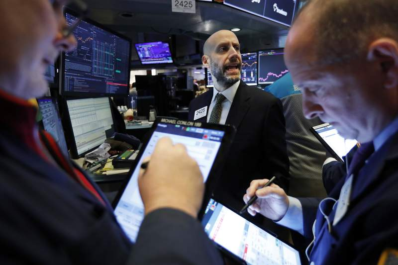 FILE - In this Feb. 6, 2020, file photo specialist Meric Greenbaum, center, works with traders at his post on the floor of the New York Stock Exchange.  The U.S. stock market opens at 9:30 a.m. EST on Tuesday, Feb. 11. (AP Photo/Richard Drew, File)