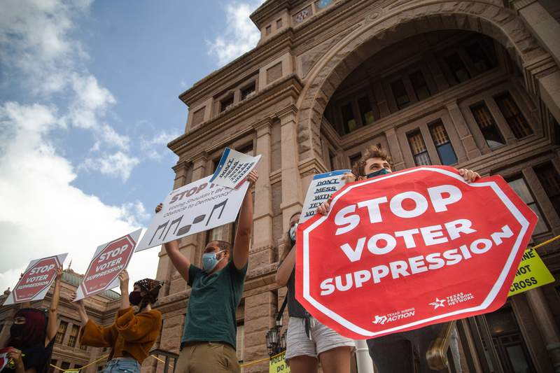 Protesters hold signs in opposition to SB 7 while participating in a rally at the state capitol on May 8, 2021.  Critics of the bill claim that the legislation suppresses voting rights by limiting and changing state voting procedures.
