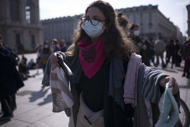 """A demonstrator wearing a protective mask from the feminist collective """"Not One Less"""" performs housework chores on March 8, 2021 in Turin, Italy. A protest of the members of the Italian feminist association takes place on International Women's Day, which grew out of the U.S. labour movement and is recognized by the United Nations to celebrate women's advancement in society."""