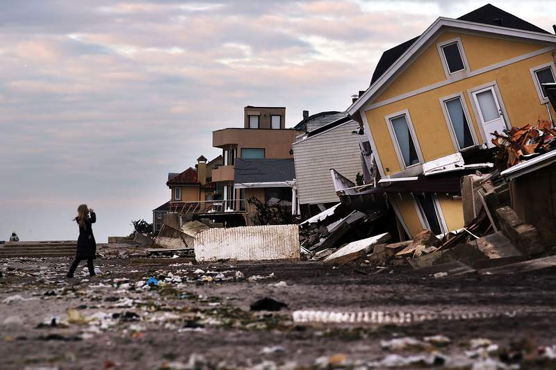 A woman walks along the beach in the heavily damaged Rockaway neighborhood, in Queens where a large section of the iconic boardwalk was washed away on November 2, 2012 in New York due to Hurricane Sandy. (Photo by Spencer Platt/Getty Images)
