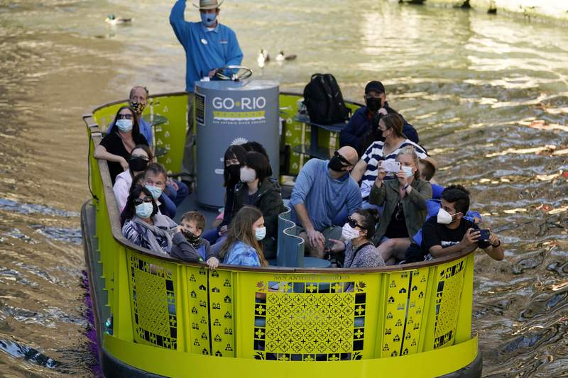 Visitors wear face masks during the coronavirus pandemic as they travel along the River Walk, Wednesday, March 3, 2021, in San Antonio. (AP Photo/Eric Gay)