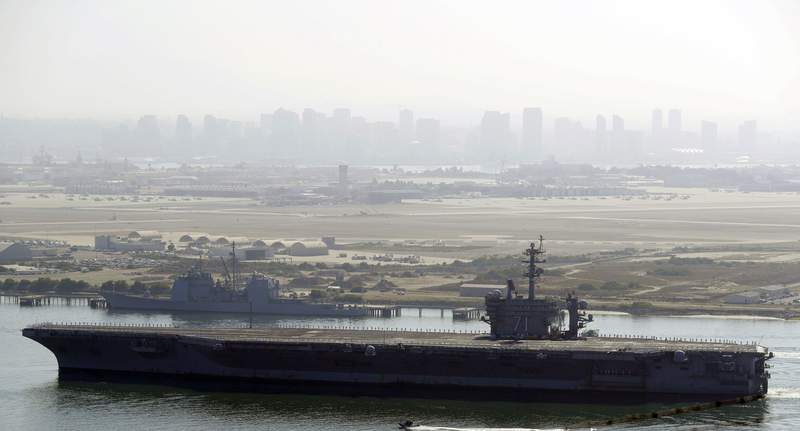 FILE - In this July 9, 2020 file photo the USS Theodore Roosevelt aircraft carrier makes its way into San Diego Bay as seen from San Diego. Three sailors aboard the USS Theodore Roosevelt have tested positive for COVID-19, the Navy said Monday, Feb. 15, 2021,  less than a year after a massive outbreak on the ship sidelined it in Guam for nearly two months. (AP Photo/Gregory Bull, File)