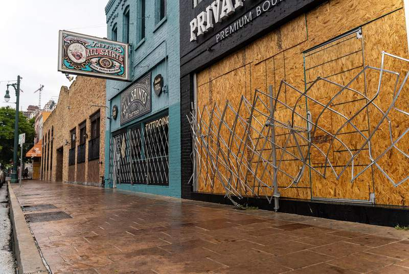 Workers boarded up bars on Sixth Street in Austin after Gov. Greg Abbott closed bars for a second time in June. After a financially devastating year, out-of-work Texans were dealt another blow this week when a congressional coronavirus relief package's fate became uncertain after President Donald Trump threatened to veto it.                    Credit: Jordan Vonderhaar for The Texas Tribune