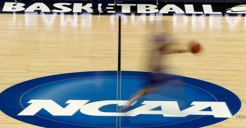 FILE - In this March 14, 2012, file photo, a player runs across the NCAA logo during practice in Pittsburgh before an NCAA tournament college basketball game. NCAA basketball administrators apologized to the womens basketball players and coaches after inequities between the mens and womens tournament went viral on social media. Administrators vowed to do better. NCAA Senior Vice President of Basketball Dan Gavitt spoke on a zoom call Friday, March 19, 2021, a day after photos showed the difference between the weight rooms at the two tournaments. (AP Photo/Keith Srakocic, File)