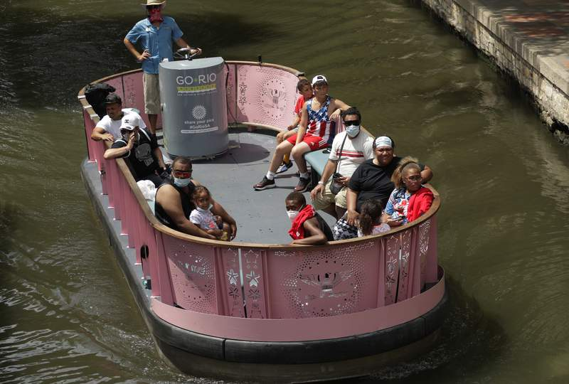 Visitors, some wearing masks to protect against the spread of COVID-19, ride a river barge along the River Walk, Tuesday, July 7, 2020, in San Antonio. Texas Gov. Greg Abbott has declared masks or face coverings must be worn in public across most of the state as local officials across the state say their hospitals are becoming increasingly stretched and are in danger of becoming overrun as cases of the coronavirus surge. (AP Photo/Eric Gay)