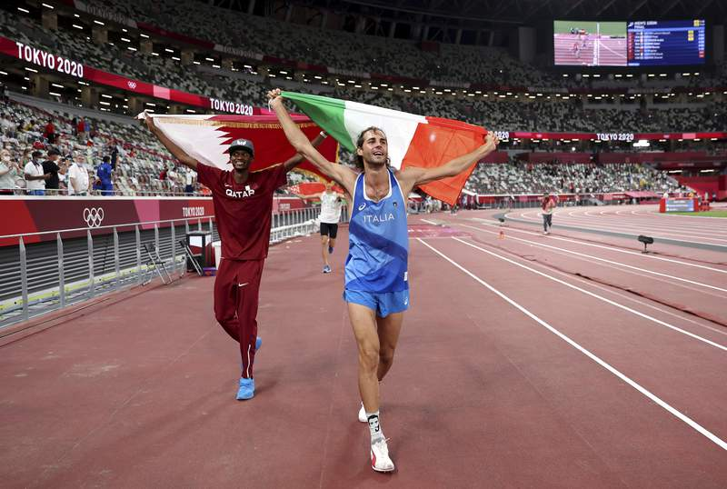 Gold medalist Mutaz Barshim, left, of Qatar and silver medalist Gianmarco Tamberi of Italy celebrate on the track after the final of the men's high jump at the 2020 Summer Olympics, Sunday, Aug. 1, 2021, in Tokyo, Japan. (Christian Petersen/Pool Photo via AP)