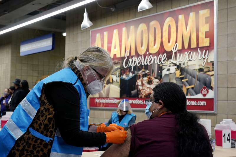 A health care worker administers a COVID-19 vaccination at the new Alamodome COVID-19 vaccine site, Monday, Jan. 11, 2021, in San Antonio, Texas. (AP Photo/Eric Gay)