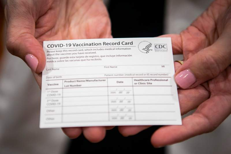 Dr. Annamaria Macaluso Davidson holds a COVID-19 vaccine registration card at Memorial Hermann Hospital in the Medical Center in Houston on Dec. 15, 2020.