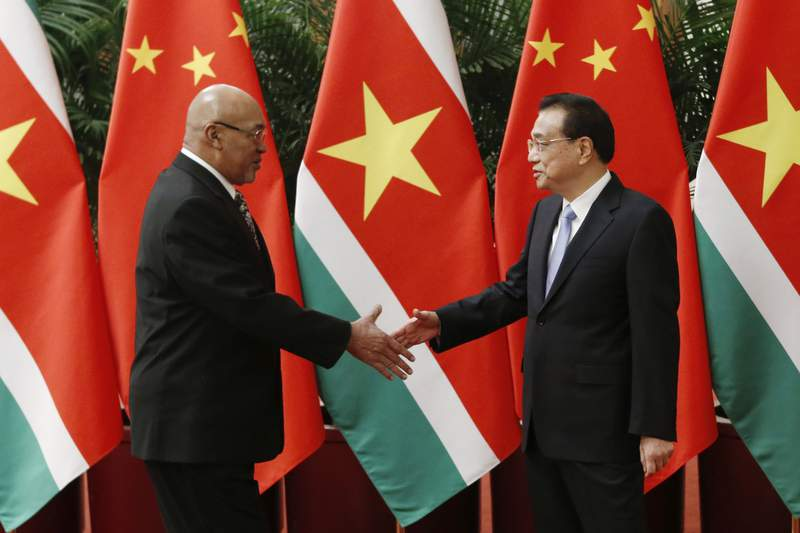 Suriname's President Desi Bouterse, left, shakes hands with Chinese Premier Li Keqiang before a meeting at the Great Hall of the People in Beijing, Wednesday, Nov. 27, 2019. (Florence Lo/Pool Photo via AP)