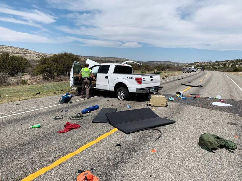 Debris is strewn across a road near the border city of Del Rio, Texas after a collision Monday, March 15, 2021. Eight people in a pickup truck loaded with immigrants were killed when the vehicle collided with an SUV following a police chase, authorities said. (Texas Department of Public Safety via AP)