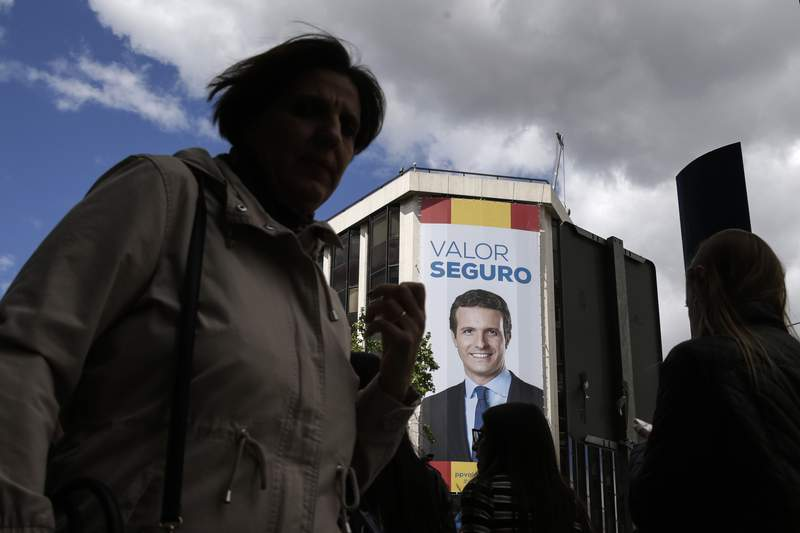 FILE - In this April 26, 2019 file photo, people walk past a banner featuring a portrait of Popular Party's election candidate Pablo Casado on the front of the Party's headquarters in Madrid, Spain. Spain's main conservative opposition Popular Party has taken its poor results in the February 2021 Catalan regional elections as a signal to make changes, starting with a decision to quit the party's long-time central Madrid headquarters in a symbolic break with past corruption cases. (AP Photo/Andrea Comas, File)
