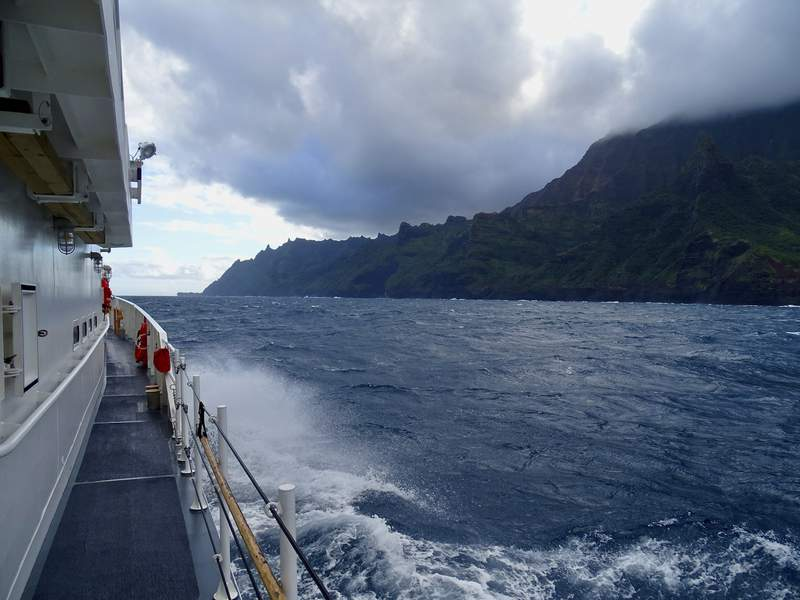 FILE - In this Dec. 27, 2019, file photo released by the U.S. Coast Guard, the Cutter William Hart moves toward the Na Pali Coast on the Hawaiian island of Kauai on the day after a tour helicopter disappeared with seven people aboard. A person who was near a remote Hawaii site where a tour helicopter crashed and killed seven people last month told investigators that visibility was only about 20 feet (6 meters) at the time because of fog and rain, according to a preliminary accident report released Wednesday, Jan. 15, 2020. (Lt. j.g. Daniel Winter/U.S. Coast Guard via AP, File)