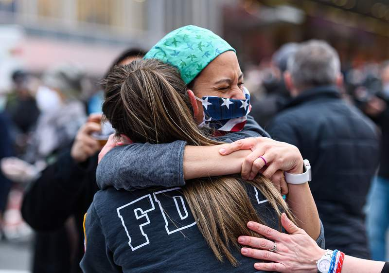 A medical worker hugs a member of the FDNY outside NYU Langone Health hospital as people applaud to show their gratitude to medical staff and essential workers during the coronavirus pandemic on April 27, 2020 in New York City.