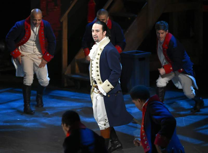"""FILE - In this June 12, 2016 file photo, Lin-Manuel Miranda and the cast of """"Hamilton"""" perform at the Tony Awards in New York.  Next year, you'll be able to see the original Broadway cast of Hamilton perform the musical smash from the comfort of a movie theater. The Walt Disney Company said Monday, Feb. 3, 2020, it will distribute a live capture of Lin-Manuel Miranda's show in the United States and Canada on Oct. 15, 2021. (Photo by Evan Agostini/Invision/AP, File)"""