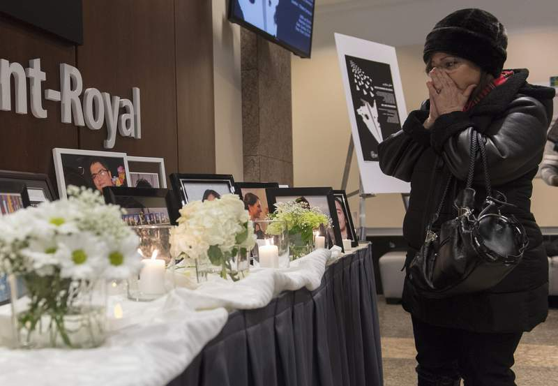 A woman pauses at a memorial prior to a ceremony in Montreal, Sunday, Jan. 19, 2020, to remember those who lost their lives in a Ukraine airplane crash in Iran on Jan. 8. (Graham Hughes/The Canadian Press via AP)