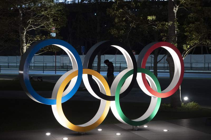 FILE - In this March 24, 2020, file photo, a man is seen through the Olympic rings in front of the New National Stadium in Tokyo. Tokyo Olympic organizers on Friday, Nov. 27, 2020 announced a series of 18 test events set to begin in March and run into May. (AP Photo/Jae C. Hong, File)