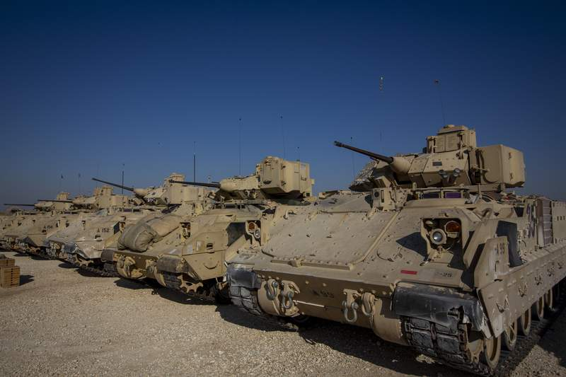 FILE - In this Nov. 11, 2019, file photo, Bradley fighting vehicles are parked at a U.S. military base at an undisclosed location in Northeastern Syria, Monday, Nov. 11, 2019. The U.S. has deployed additional troops and armored vehicles into eastern Syria after a number of clashes with Russian forces, including a recent vehicle collision that injured four American service members. (AP Photo/Darko Bandic, File)