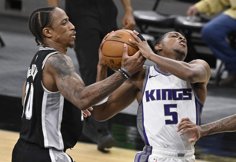 San Antonio Spurs' DeMar DeRozan, left, strips the ball from Sacramento Kings' De'Aaron Fox during the second half of an NBA basketball game Wednesday, March 31, 2021, in San Antonio. (AP Photo/Darren Abate)