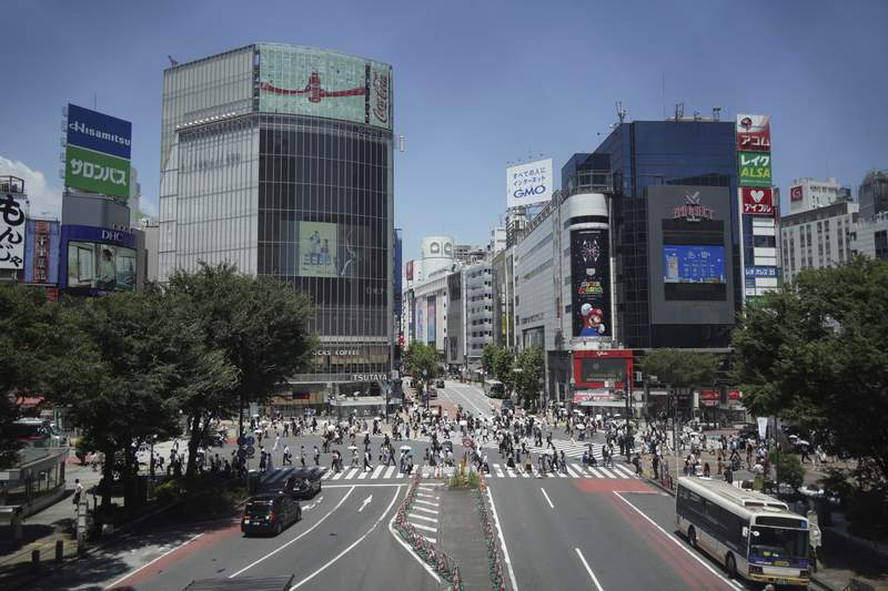People walk across Tokyo's Shibuya scramble crossing on Wednesday, July 21, 2021. COVID-19 cases are rising in Tokyo, recording over 1,300 new cases on Tuesday, even with the fourth state of emergency imposed for the entire period of Olympic games. (AP Photo/Kantaro Komiya)