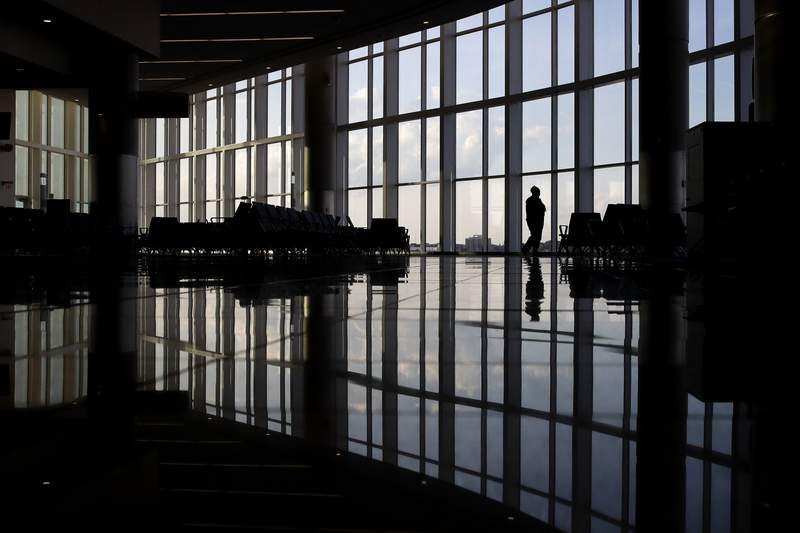FILE - In this Monday, June 1, 2020 file photo, a woman looks through a window at a near-empty terminal at an airport in Atlanta. Anxiety and depression are rising among Americans compared with before the pandemic, research suggests. Half of those surveyed in a study released on Wednesday, Sept. 2, 2020, reported at least some signs of depression. (AP Photo/Charlie Riedel)