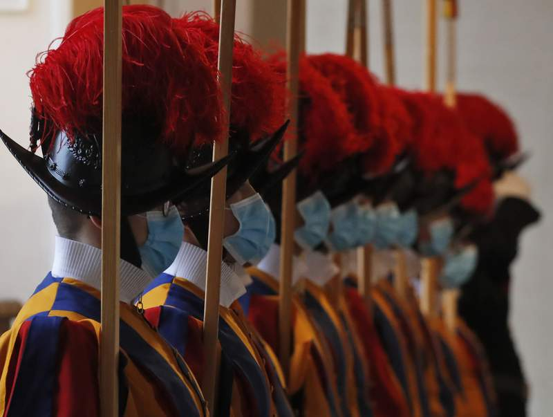 FILE - In this Saturday, Oct. 24, 2020 file photo, Vatican Swiss Guards wear masks to curb the spread of COVID-19 as they stand attention at the Vatican. Three Vatican Swiss Guards who have refused to be vaccinated against COVID-19 upon Holy See orders and have left the storied corps to return to Switzerland. A Swiss Guard official, Lt. Urs Breitenmoser told The Associated Press on Sunday all Swiss Guards were asked to be vaccinated to protect their health and that of the others they come into contact as part of their service. (AP Photo/Alessandra Tarantino, File)