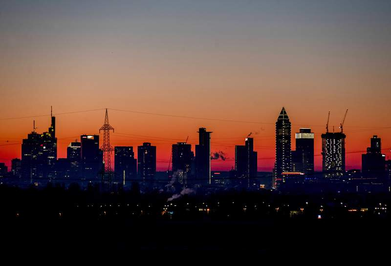 FILE - In this Feb.14, 2021 file photo the sun is about to rise behind the buildings of the banking district in Frankfurt, Germany. The European statistics agency Eurostat released monthly inflation figures Tuesday.(AP Photo/Michael Probst, file)