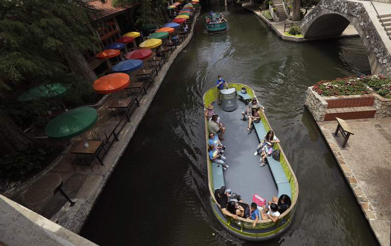 Using social distancing and other protective measures against COVID-19, visitors ride a river barges along the River Walk in San Antonio, Monday, June 15, 2020, in San Antonio. (AP Photo/Eric Gay)