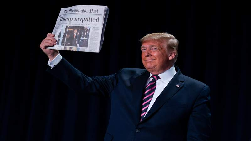 """President Donald Trump holds up a newspaper with the headline that reads """"Trump acquitted"""" during the 68th annual National Prayer Breakfast, at the Washington Hilton, Feb. 6, 2020, in Washington."""