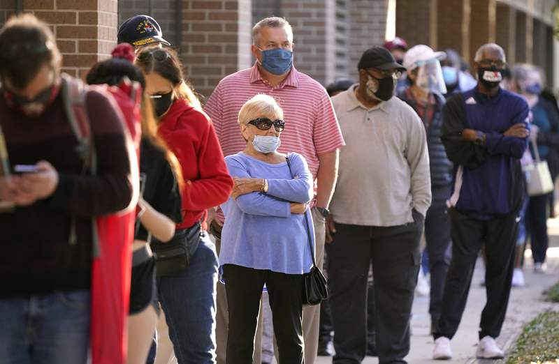 Voters line up outside Richardson City Hall for early voting Tuesday, Oct. 13, 2020, in Richardson, Texas. (AP Photo/LM Otero)