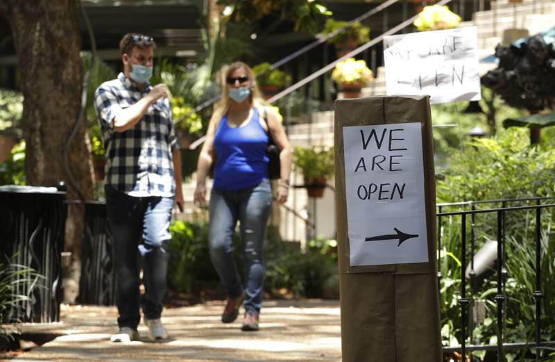People wearing a face masks for protection against COVID-19 pass a business that has reopened in San Antonio, Thursday, May 14, 2020. (AP Photo/Eric Gay)