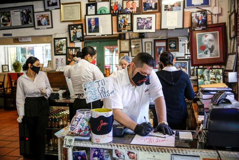 Juan Meza take a to-go order at Juan In A Million in May in Austin. Texas businesses will be allowed to operate at 100% capacity next week and can decide whether to require customers to wear masks. (Credit: Bronte Wittpenn/American-Statesman via USA TODAY NETWORK)